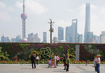 Skyline of Pudong looming above Floral Wall and surveillance cameras on Bund in Shanghai.