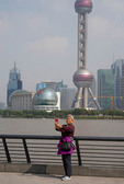 Elderly Chinese woman taking a selfie with Oriental Pearl Tower and skyline of Pudong across Huangpu River in Shanghai.