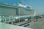 New Shanghai Baoshan Cruise Terminal with Royal Caribbean's mega cruise ship Quantum of the Seas towering over it.