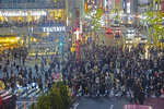 """Pedestrians walking diagonally through the intersection during """"the scramble"""" at Shibuya Crossing in downtown Tokyo at night."""