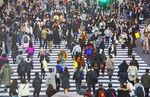 "Pedestrians walking diagonally through the intersection during ""the scramble"" at Shibuya Crossing in downtown Tokyo."