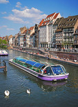 Sightseeing tour boat cruising the canals of Strasbourg, France.