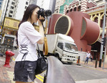 Young Asian woman tourist photographing on street in Hong Kong.