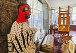 A Frida Kahlo papier-mache folk art sculpture stands next to her easel and wheelchair in her workshop in the Frida Kahlo Museum in Mexico City.