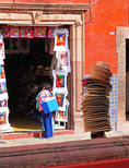 Shop selling Frida Kahlo t-shirts in Centro San Miguel de Allende with man of many hats passing through.