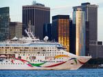 Norwegian Dawn cruise ship passing lower Manhattan skyline in New York Harbor.