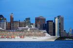 Oceania Cruises' Riviera cruise ship passing lower Manhattan skyline in New York Harbor at dusk.