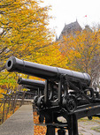 Cannons on wall of Old Quebec City with Chateau Frontenac in background in autumn.