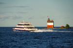 Mackinac Island ferry of Star Line passing Round Island Lighthouse in Straits of Mackinac from Mackinaw City, Michigan.