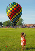 Small girl waving to hot air balloon about to ascend.