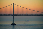San Francisco Bay Bridge at dusk with schooner and freighter in bay.