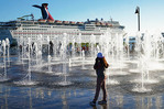 Fountain on waterfront in Ensenada, Mexico, with Carnival Inspiration cruise ship in port.