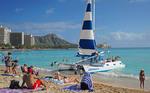 Catamaran cruise boat picking up passengers on Waikiki Beach in Honolulu, Hawai'i.