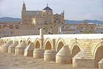 Roman bridge over muddy Guadalquivir River to Great Mosque and Cathedral in Cordoba, Spain.