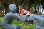 Girl on Statue at Temple of Literature, Hanoi, Vietnam