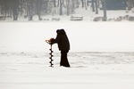 Drilling hole in ice for Ice Fishing on Lake Geneva, Wisconsin