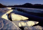 Sunlight on icebergs in Kongakut River at midnight in early summer, Brooks Range in background.