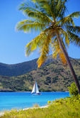 Sailboat passing between Sandy Cay and Jost Van Dyke Island.  British Virgin Islands.  Caribbean.