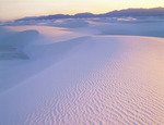 Wind ridges in gypsum dunes at sunset with San Andres Mountains. White Sands National Monument, New Mexico.