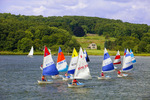 Teenagers in fleet of small sailboats racing in the Mystic River.  Mystic, Connecticut.