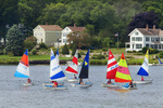Children in fleet of racing sailboats in the Mystic River, with historic houses in background. Mystic, Conecticut.
