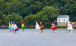 Children in fleet of racing sailboats in the Mystic River.  Mystic, Conecticut.