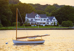 Wooden catboat moored in the Mystic River, with historic house.  Mystic, Connecticut.