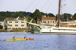 Kayakers in the Mystic River with the three masted barquentine,  'Mystic'.   Mystic, Connecticut.