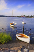 Mystic River with small sailboats at sunset from downtown Holmes Street.   Mystic Seaport in background.  Mystic, Connecticut.