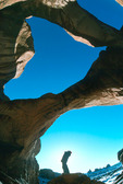 Glenn Randall looks up at Double Arch, Arches National Park, Utah