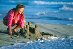 Atmospheric research scientist Cora Randall building a sand castle on Manresa Beach, Monterey Bay, near Santa Cruz, California