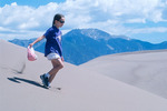 Girl running down a sand dune at Great Sand Dunes National Park, Colorado