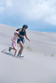 Mother and daughter running down a sand dune, Great Sand Dunes National Park, Colorado
