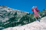 Girl running down boulder, Rocky Mountain National Park, Colorado