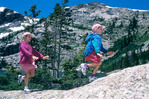 Girls playing on boulder, Rocky Mountain National Park, Colorado