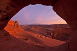 Delicate Arch through natural window at sunset, Arches National Park, Utah