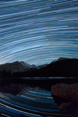 Star trails over Longs Peak and Glacier Gorge, reflected in Bear Lake, Rocky Mountain National Park, Colorado
