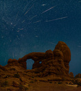 Perseid meteors over Turret Arch, Arches National Park, Utah. This image is a composite of 49 meteors shot on the nights of August 10-11, 11-12, and 12-13, 2018. Almost all of the meteor images, plus the land image and background sky image, were shot from the same camera position on the west side of Turret Arch. A few of the meteors were shot from a second camera position, also on the west side of Turret Arch about 50 yards from the first camera position.