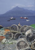 Fishing boats and lobster creels on the dock at Elgol, Isle of Skye, Scotland.  Black Cuillins in the distance.