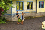 Local kids carry a basket of fruit in Savaii Western Samoa