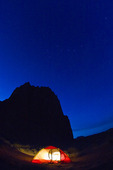 Tent lights up under the Temple of the Sun in Capitol Reef National Park Utah