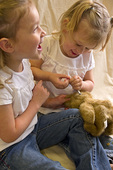 Two young girls practice giving their insulin shots on a plush bear