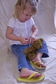 Young diabetic girls practices giving insulin on her plush bear