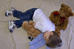 Young diabetic boy takes a nap with some of his favorite plush friends