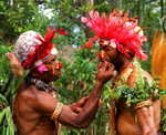 Colorful performers applying makeup at Sing-Sing festival, Highland Papua New Guinea