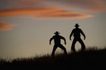 Cowboys drawing their guns against a Wyoming sunset.
