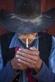Cowboy lighting cigarette showing working hands. Wyoming.