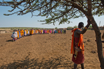 Maasai Warrior watching women performing traditional dance.  Tribal Maasai women in traditional dance. Maasai Mara Natioanal Reserve.  Kenya, Africa.