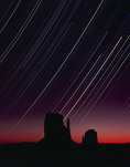 Star tracks and pre-dawn glow over the Mittens, Monument Valley, Arizona