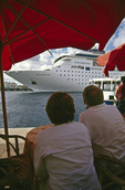 Tourists watch a departing cruise ship, from a cafe on the Handelskade, Willemstad, Curacao
